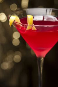 Cosmopolitan cocktail with lemon garnish in front of a gold glitter background